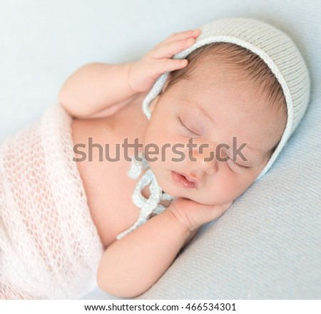 lovely newborn baby sleeping in hat with hands on head