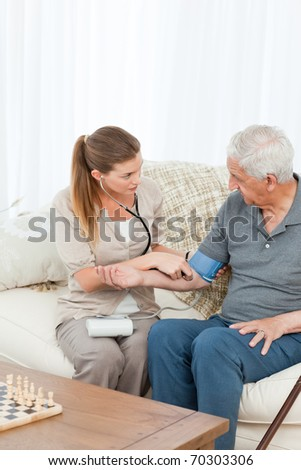 Lovely nurse helping her patient to do exercises at home