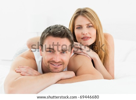 Lovely pairs lying down together in their bed at home - stock photo