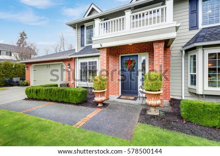 Lovely Pale Green Colonial Home Features Red Brick Porch With Columns Attached Garage And Well