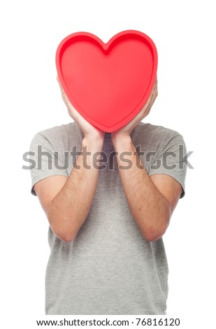 lovely portrait of a young man holding a red heart (isolated on white background) - stock photo