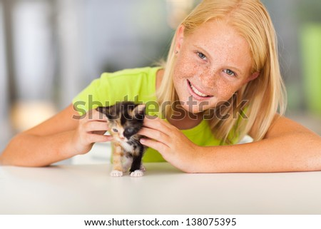 lovely pre teen girl with pet kitten at home - stock photo