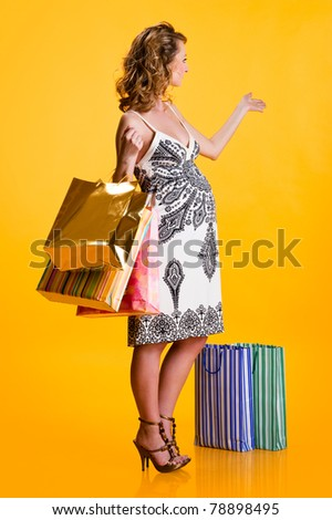 Lovely pregnant woman with shopping bags gesturing indoors - stock photo