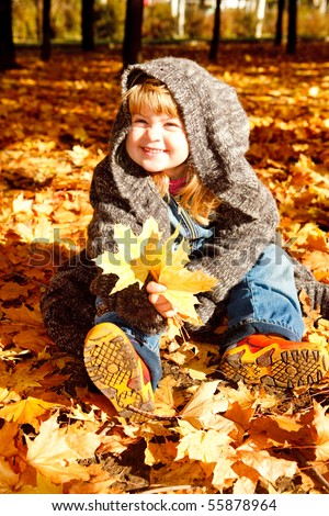 Lovely preschool girl sitting in an autumn park - stock photo