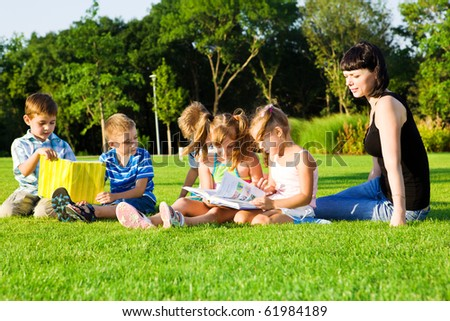 Lovely preschoolers with books, teacher beside them - stock photo