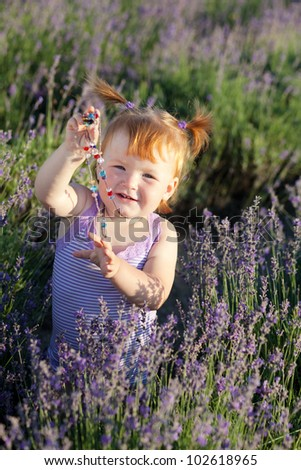 Lovely red hair little girl with beads in a lavender field - stock photo