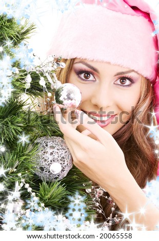 lovely santa helper girl decorating christmas tree - stock photo