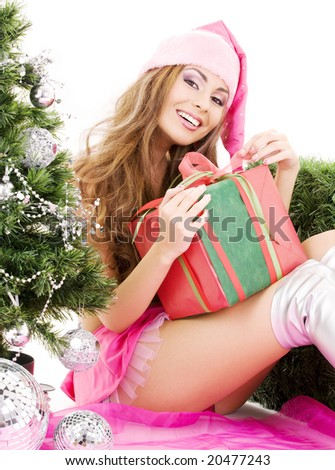 lovely santa helper girl with gift box and christmas tree - stock photo