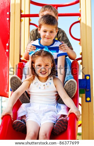Lovely school aged children on the chute - stock photo