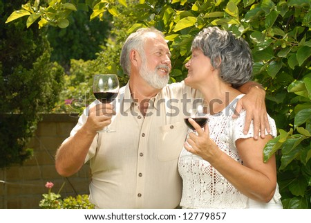 Lovely senior couple dining al fresco with wine glasses - stock photo