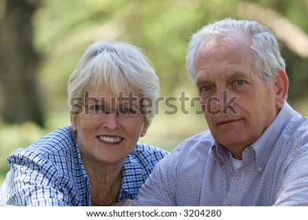 Lovely senior couple outdoors on a summerday (focus on woman) - stock photo