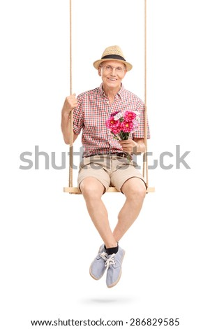 Lovely senior gentleman sitting on a swing and holding a bouquet of flowers isolated on white background - stock photo