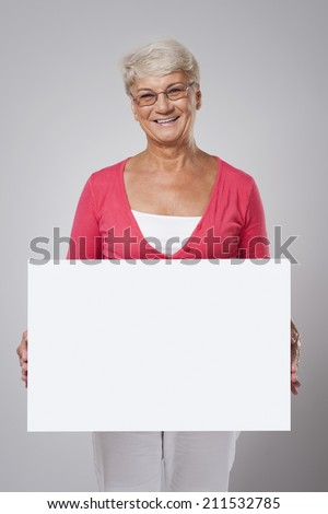 Lovely senior woman covering by whiteboard  - stock photo