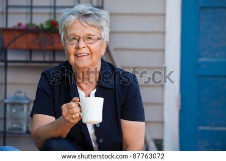 Lovely senior woman having a cup of tea - stock photo