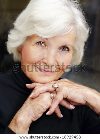 Lovely senior woman portrait on dark background, looking graciously - stock photo