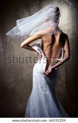 Lovely sensual bride unzip her wedding dress - stock photo