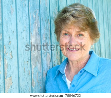 Lovely Seventy Year Old Woman Smiling in Blue Shirt with Copyspace or Room for your words or text - stock photo