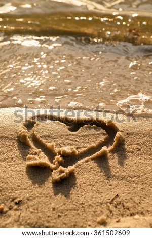 Lovely small heart drawn in salt  sand at beach. Evening warm colors of sun mirror in water level. - stock photo