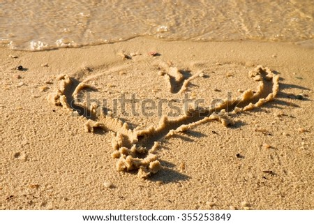 Lovely small heart sketched in salt  sand at beach. Evening warm colors of sunset mirror in water level. - stock photo