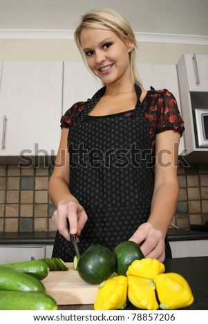 Lovely smiling blond housewife preparing vegetables in the kitchen - stock photo