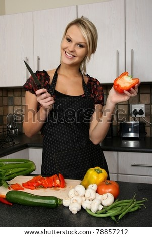 Lovely smiling blond housewife preparing vegetables in the kitchen
