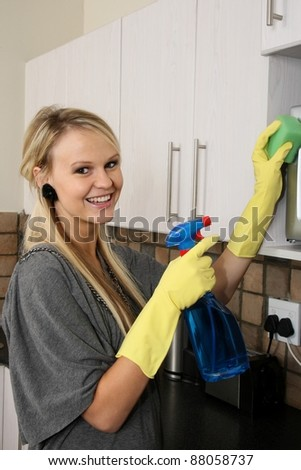 Lovely smiling blond lady cleaning her kitchen