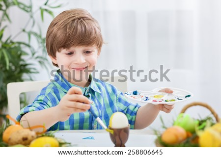 Lovely smiling child painting eggs for easter - stock photo