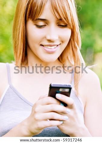 lovely smiling girl reads sms on mobile phone, against green summer garden. - stock photo
