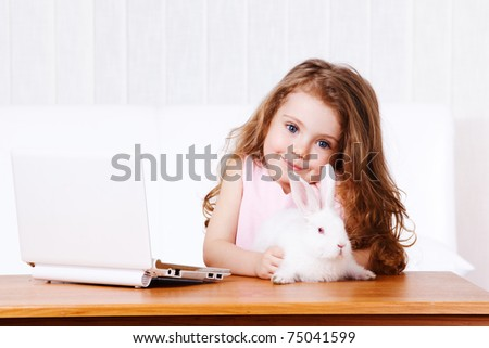 Lovely smiling girl with white rabbit and laptop - stock photo