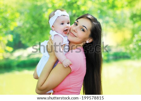 Lovely smiling mother with baby in summer sunny day - stock photo