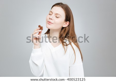 Lovely smiling teenage girl with eyes closed eating chocolate  - stock photo