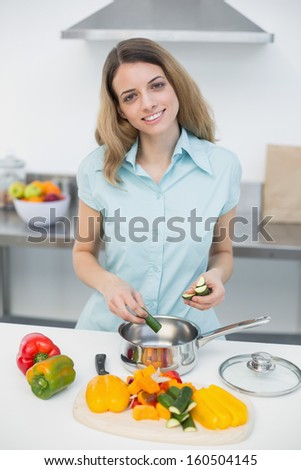Lovely smiling woman cooking standing in kitchen smiling cheerfully at camera