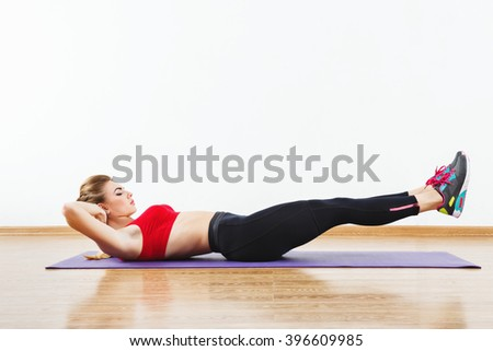 Lovely sportive girl wearing snickers, black leggings and red short top doing side leg raise on purple matt at gym, fitness, white wall and wooden floor, white background. - stock photo