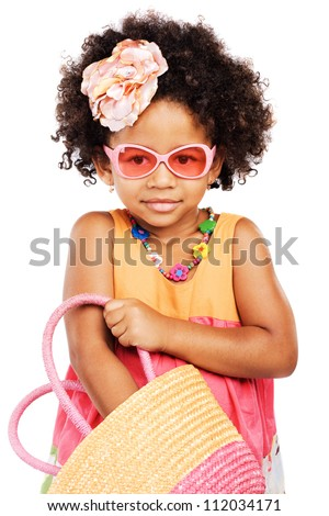 Lovely stylish little girl getting something from her straw bag - stock photo