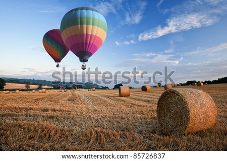 Lovely sunset golden hour landscape of hay bales in field in English countryside - stock photo