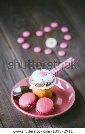 Lovely sweet dessert with small almond cake, pink raspberry french macaroons and candies on rustic wooden table. - stock photo