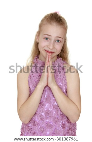 Lovely teen girl with blond hair loose around her palms face. A girl dressed in a pink dress, close-up-Isolated on white background - stock photo