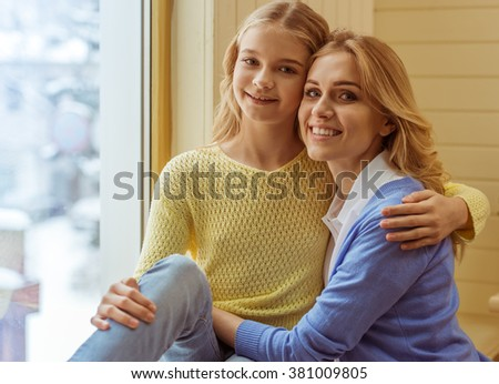 Lovely teenage girl and her beautiful mother cuddling, looking at camera and smiling - stock photo