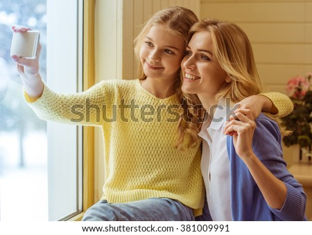 Lovely teenage girl and her beautiful mother cuddling, making a photo and smiling - stock photo