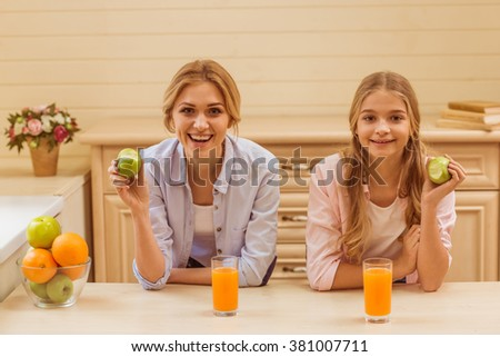 Lovely teenage girl and her beautiful mother eating apples, looking at camera and smiling while sitting in the kitchen - stock photo