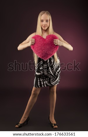 Lovely teenage girl on black background with a heart on Valentines Day.