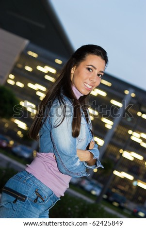 Lovely teenage girl posing in front of shopping mall in the night. - stock photo