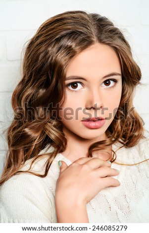 Lovely teenager girl with beautiful long curly hair wears white knitted  jersey. Beauty, fashion