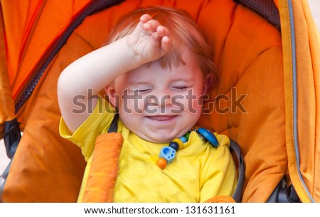 Lovely toddler boy smiling outdoor in orange stroller in summer