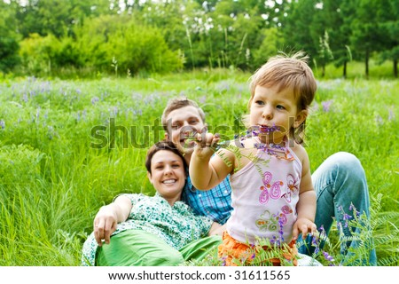 Lovely toddler eating flower, smiling parents in back - stock photo