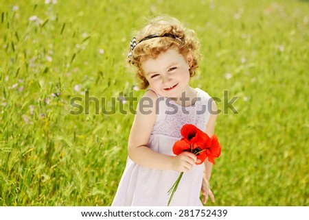 lovely toddler girl in field of grass with flowers - stock photo