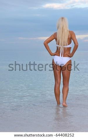 lovely trim blonde female bikini model on florida gulf coast beach at dawn - stock photo