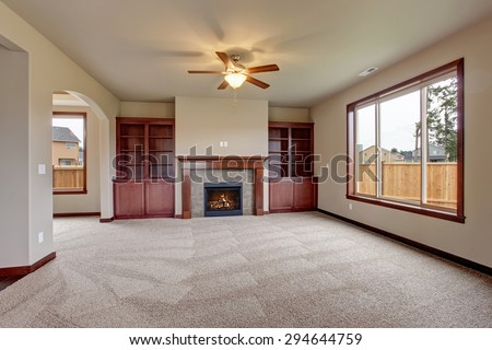 Lovely unfurnished living room with stained wood cabinets and fireplace. - stock photo