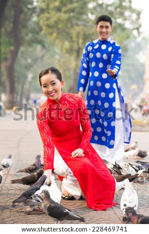 Lovely Vietnamese couple in traditional clothes feeding pigeons