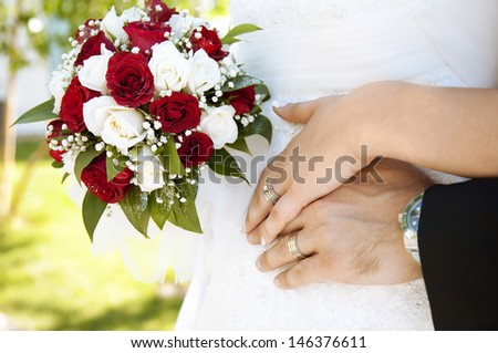 Lovely wedding couple's hands, rings and flower.